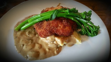Chicken schnitzel with mashed potato, mushroom sauce and broccolini